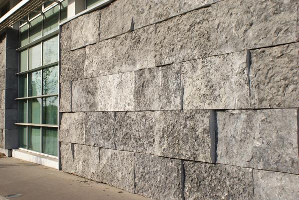 Avec son aspect rugueux, la croûte de pierre bleue donne l'impression de gros blocs parfaitement équarris. Il ne s'agit pourtant que de dalles de 10 cm d'épaisseur, fixées sans joint à des équerres métalliques. / Lille / conception Architectes associés Meas - Windels - Quatr'a - Couturon